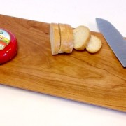 cherry bread board with cheese and a knive