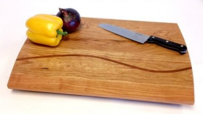 Cherry cutting board with curved walnut accent