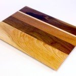 cherry, walnut and mahogany cutting board with maple stripe