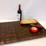 Large walnut butcher block displayed with food items and wine.